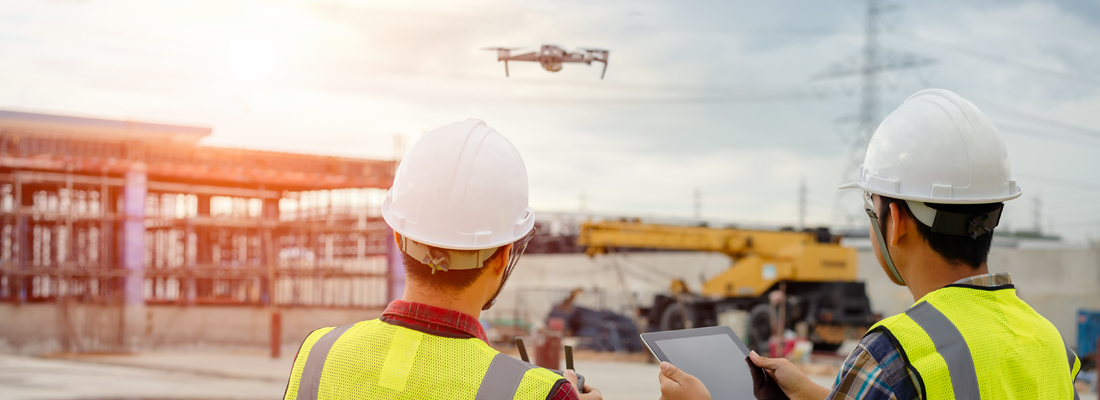2 construction men flying a drone